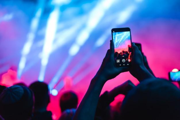 音楽コンサートでスマートフォンを使ってビデオを録画する人々