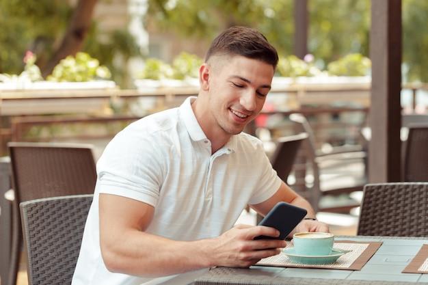 若い男がカフェでスマートフォンを使用して