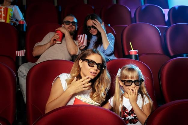 ポップコーンと飲み物の映画館に座っている友人のグループ