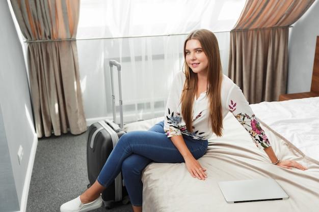 Молодая женщина, лежа в кровати гостиничного номера
