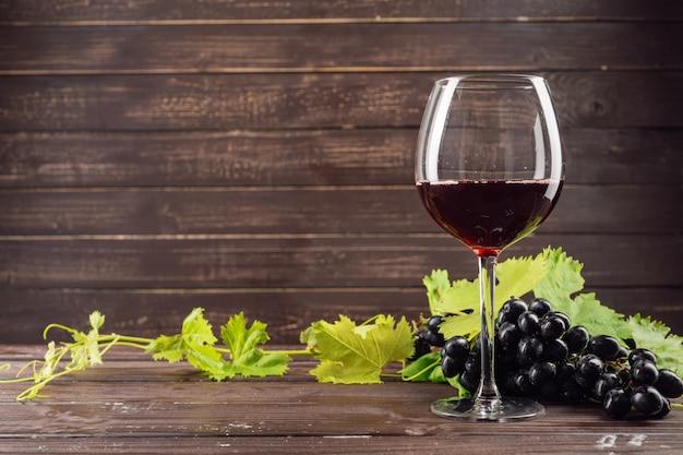 ワイングラスと木製のテーブルの上にブドウの房