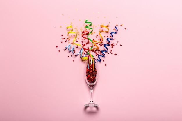 お祝いのフラットレイアウト。シャンパングラス、カラフルなパーティーの吹流し