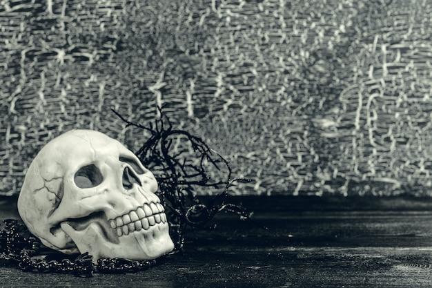 ハロウィーンの人間の頭蓋骨、古い木製のテーブル