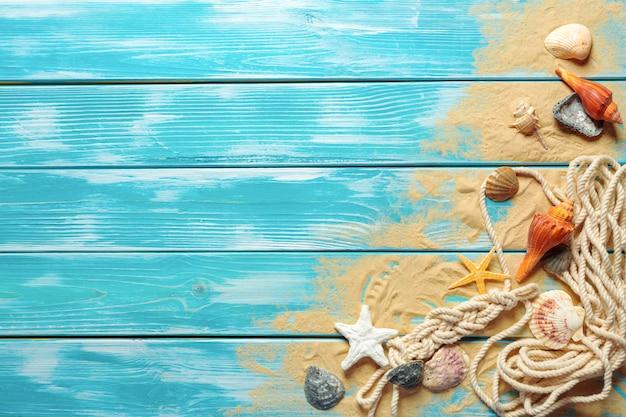 Морская веревка с множеством различных морских раковин на морской песок на синем деревянный вид сверху