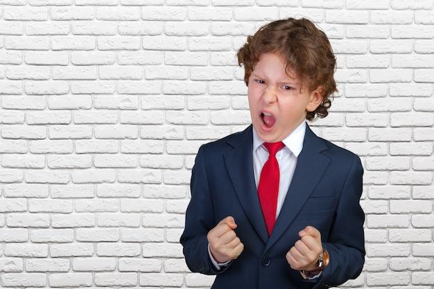 フォーマルなスーツで怒っている巻き毛の少年