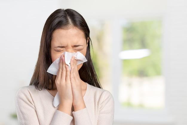 風邪をひいているハンカチを持つ若い女