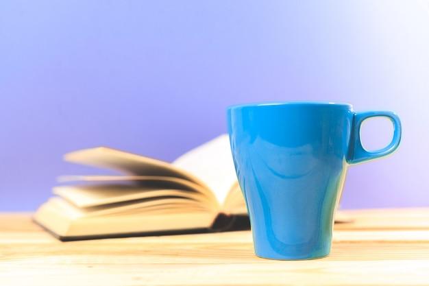 テーブルの上の本と紅茶の色カップ