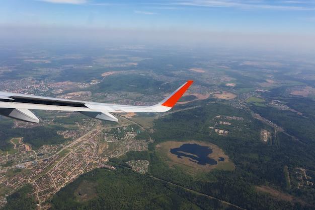 飛行機の窓から青い雲と飛行機の翼の眺めの空撮。