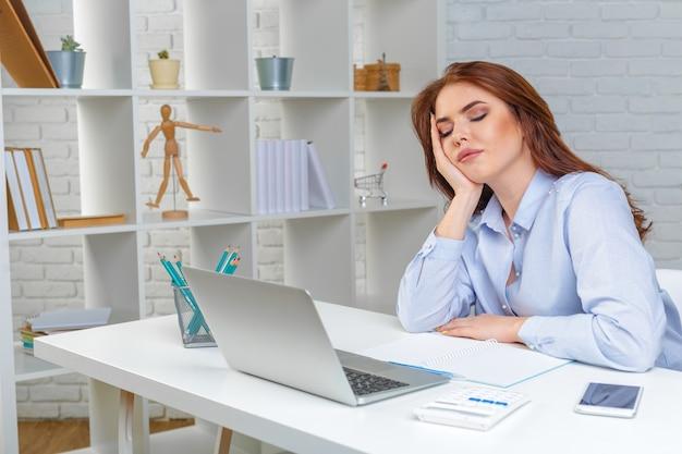Красивая утомленная бизнес-леди спать на работе
