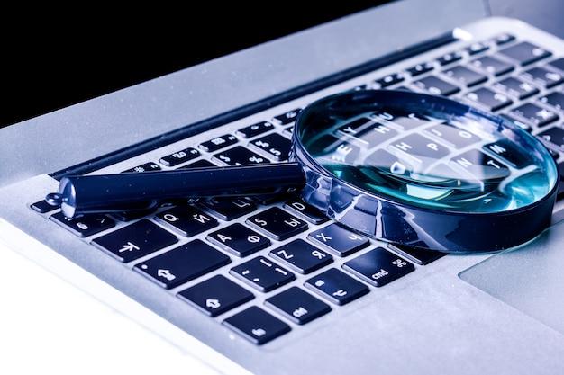 ノートパソコンのキーボードの虫眼鏡のクローズアップ画像