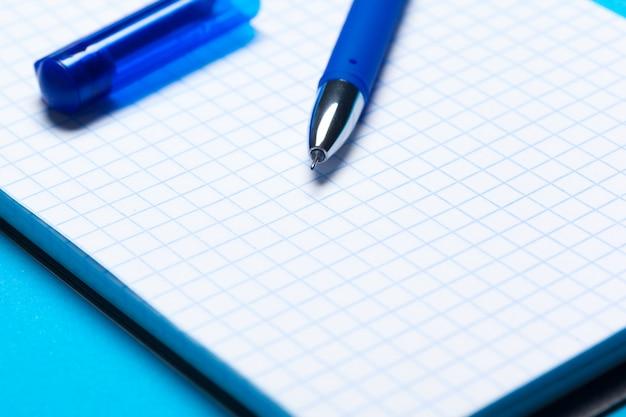 ノートブック、ペンと青のトップビューワークスペースモックアップ