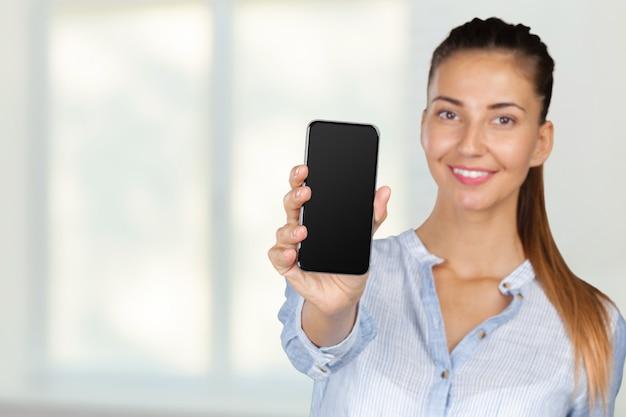 携帯電話を持つ若い女性の笑みを浮かべてください。