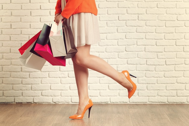 カラフルな買い物袋を運ぶ若い女性の足のショットを閉じる