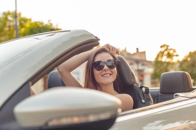 街で晴れた日にコンバーチブルカブリオ車で美しい少女