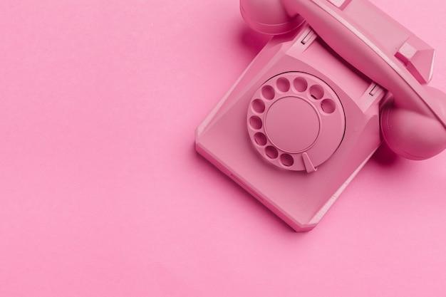 Старинный телефон на розовом
