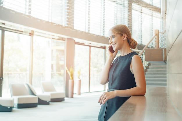 Женщина с помощью мобильного телефона в офисе