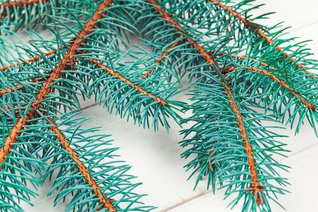 木の板にクリスマス松の木の枝。