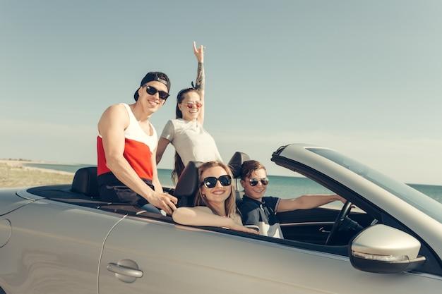 Улыбающиеся друзья за рулем автомобиля возле моря и с удовольствием