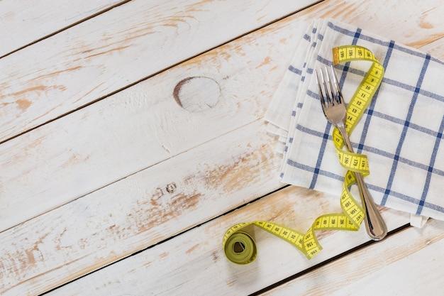 木製の背景に測定テープ。ダイエットの概念