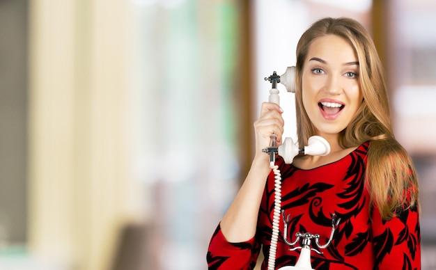 レトロな電話を持つ若い女