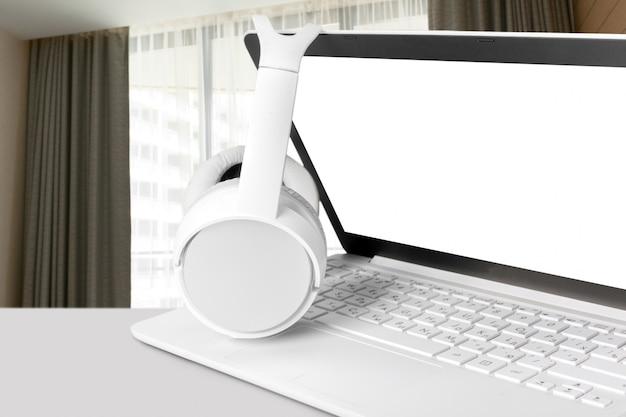 テーブルの上のノートパソコンとヘッドフォン