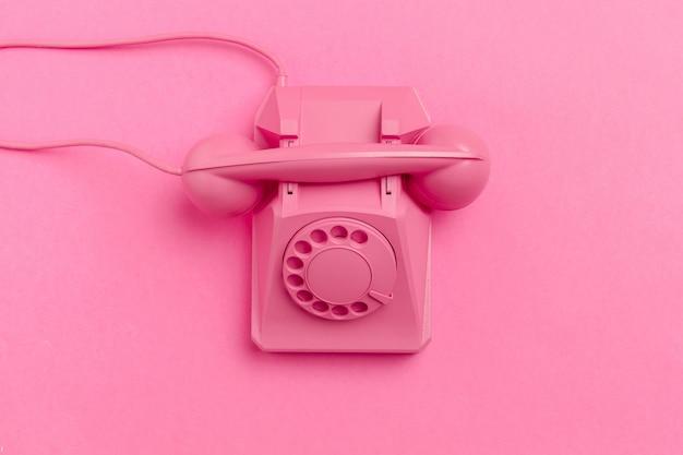 Винтажный телефон на пастельно-розовом