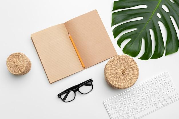 Рабочая область с клавиатурой, пальмовым листом и аксессуарами. плоская планировка, вид сверху