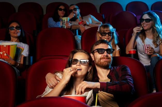 映画館に座っている友人は、ポップコーンを食べたり水を飲んだり映画を見ます。