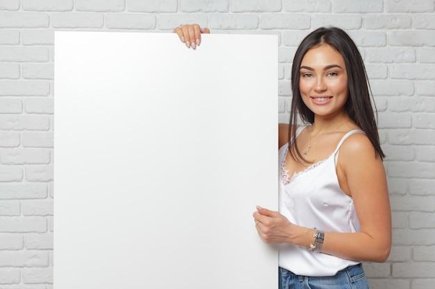 コピースペースで大きな空白のホワイトボードを保持している若いブルネットの女性