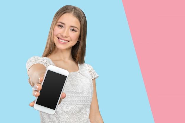 空白のスマートフォンの画面を見せて幸せなきれいな女