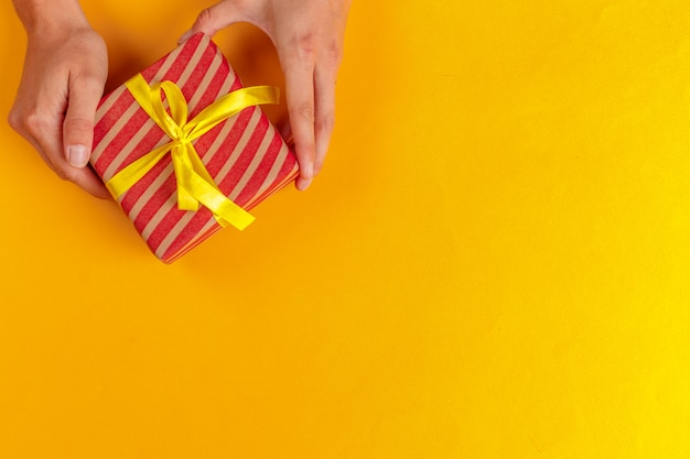 Женщина, держащая подарочную коробку на желтом