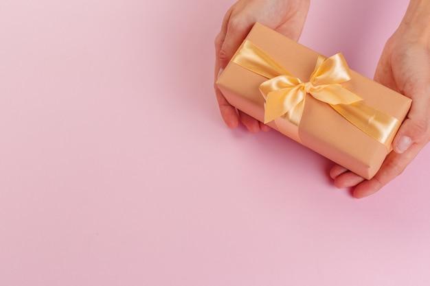 Женщина, держащая подарочной коробке на розовом