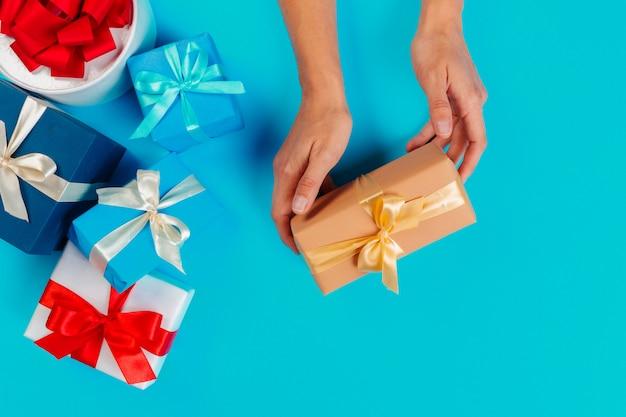 Женщина, держащая подарочной коробке на синем