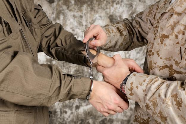 Американский солдат арестовывает преступника / террориста, надев наручники