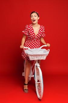 Красивая девушка в стиле пин-ап с велосипедом