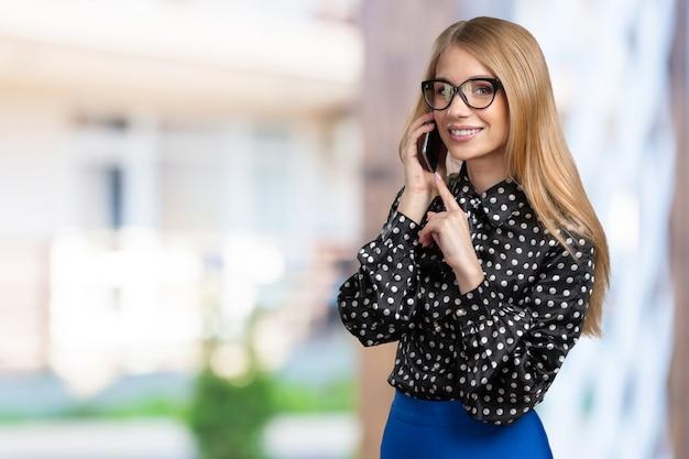 電話を話して笑顔のビジネス女性の肖像画
