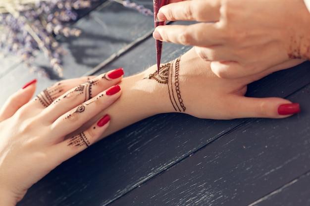 女性の手に一時的な刺青を適用するプロセス
