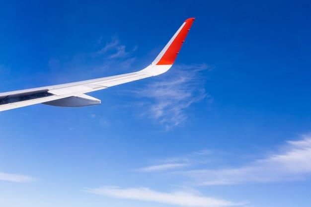 Вид из окна самолета с голубым небом и белыми облаками