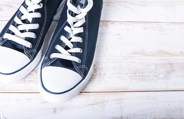 白の木製の背景にひもを持つ若者の古典的なための半靴