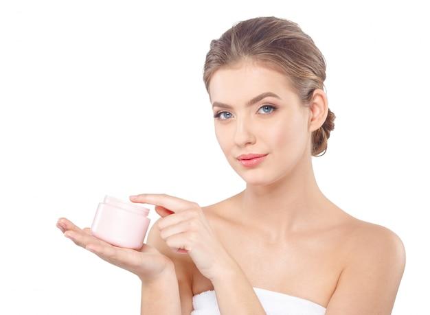 Женщина с кремом по уходу за кожей лица