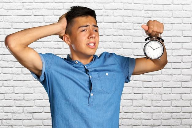 目覚まし時計を保持している若い男