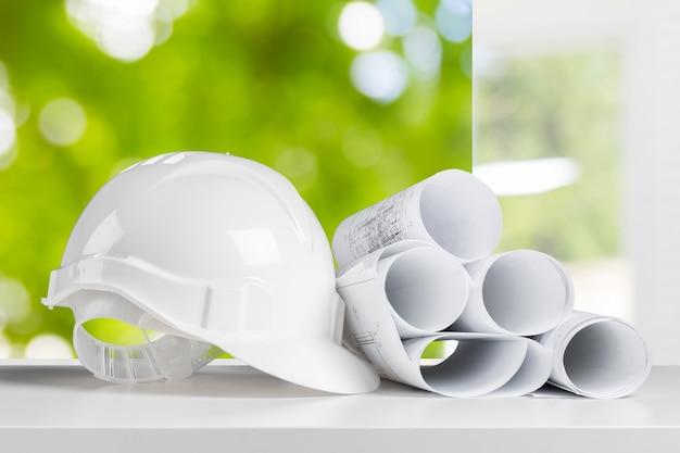 安全ヘルメットと建築家の作業テーブル