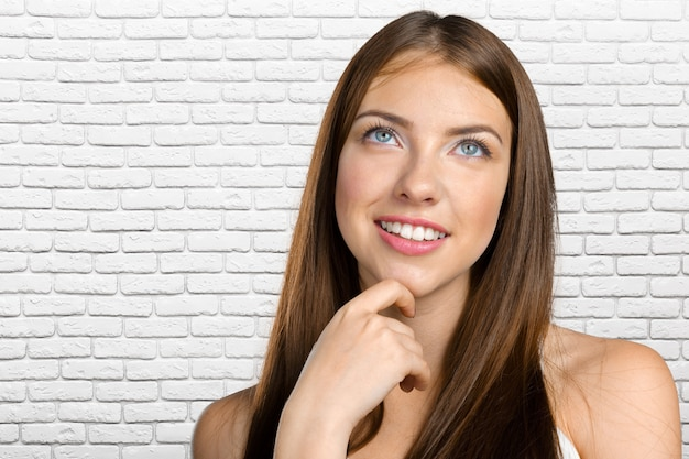 Портрет привлекательной молодой женщины, думая глубоко