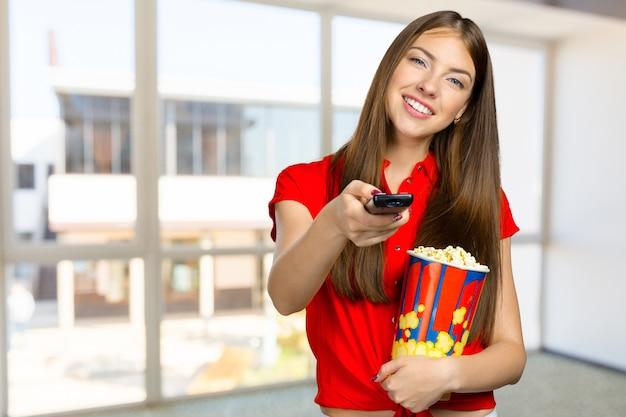 Девочка ест попкорн и смотрит телевизор