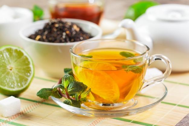 ミントと紅茶のカップを木製のテーブルの上葉します。
