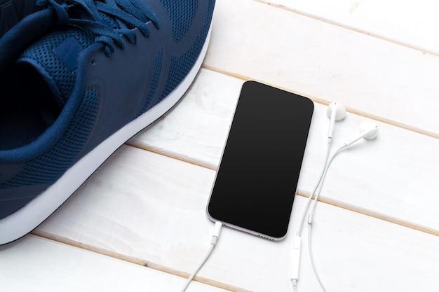 スニーカーとヘッドフォン付き携帯電話