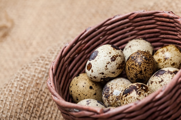 Свежие перепелиные яйца на деревянной тарелке