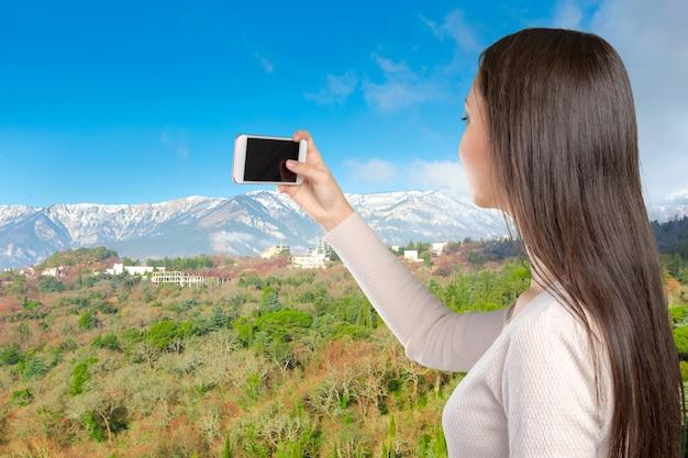 Улыбающаяся молодая женщина с мобильным телефоном