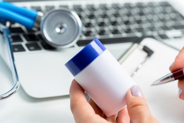 女医医師の手は薬の瓶を保持します