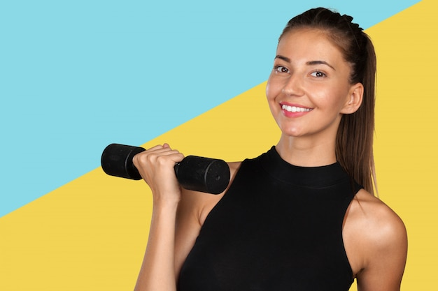 ダンベルとフィットネストレーニングをしている若い女性
